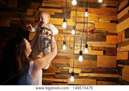 Mother with baby boy near decor incandescent lamps light