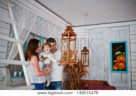 Young Caucasian Happy Family  Background Suspended Candlesticks And Wooden Ladder With Different Dec