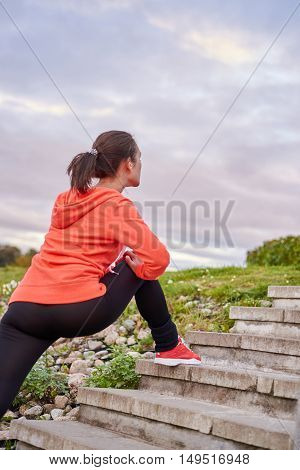 Stretching legs after jogging. Professional sportsmen woman have training in the morning outdoor in the town. Street fitness workout concept.