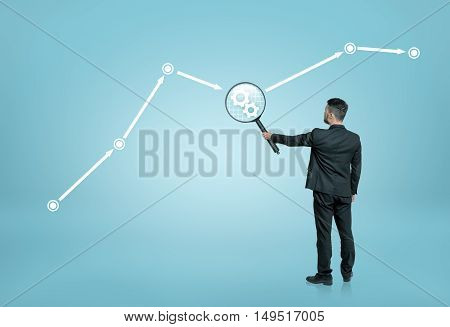 Back view of a businessman looking at cogwheel through a magnifier. Teamwork.