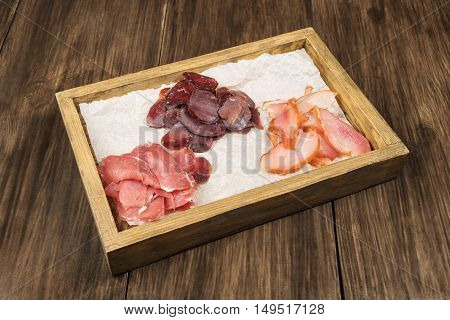 Smoked meat is of three kinds chicken pork and beef in a wooden box on the table