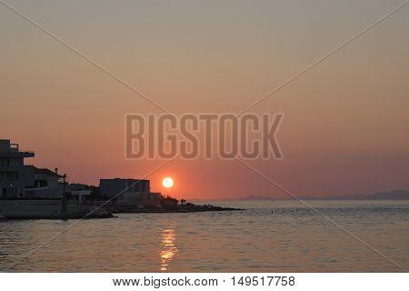 Sunset in Postira harbor on Brac Island in Croatia.