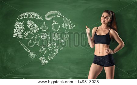 Slim girl showing thumb up on the background of painted fruits and vegetables. Slim and healthy body. Healthy lifestyle concept. Proper nutrition.