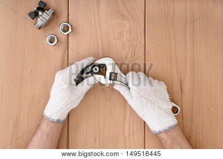 Close-up of male hands holding the ball valve and a wrench. Plumber and master. Construction and utilities. Piping works.