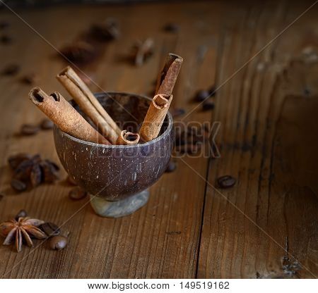 star anise, cinnamon in a cup on a wooden background