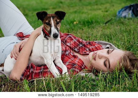 Smiling pretty 20-25 years girl in tartan red shirt with long hair lies on the grass with her active foxterrier. side view