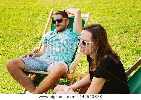 Happy Young Smiling People Relaxing and Communicate Outdoor on the Background with Green Grass. Park or Outdoor Cafe. Studing Communicate Holidays Vacation Love and Friendship Concept. Focus on a Woman