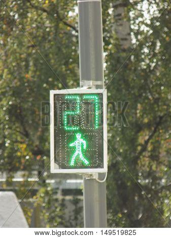 City pedestrian traffic light showing green light