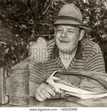 Sepia toned outdoor portrait of positive and smiling elderly man bee-keeper wearing straw hat