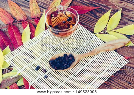 Drink From Dried Hawthorn Berries In Wooden Spoon On The Table With Colorful Autumn Leaves. Top View Closeup. Tinted image. Autumn concept