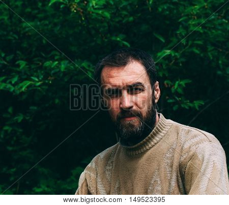portrait of a pensive adult male with gray hair in his beard against the backdrop of green foliage. toned image