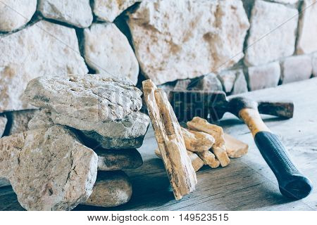 Construction Hammer And Stack Flagstone Against The Wall Of Stone Closeup. Concept Building Repair