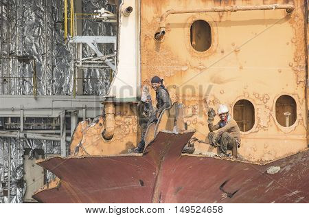 Chittagong Bangladesh February 24th 2016: workers on a partially broken down ship
