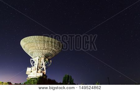 huge white satellite antenna radio telescope on the background of star