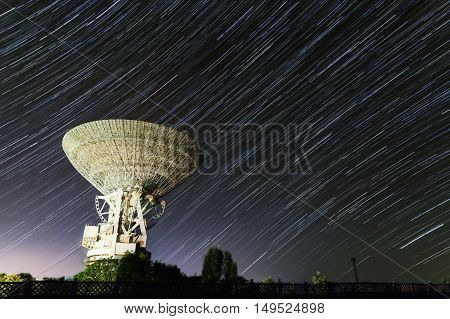 huge white satellite antenna radio telescope on the background of stellar tracks