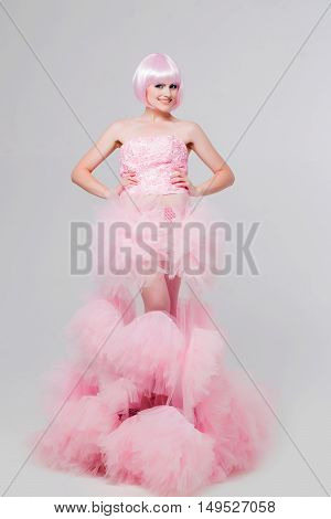 sexy glamour girl or woman with fashionable makeup on pretty face and short hairstyle or pink wig in dress posing as doll in studio on grey background