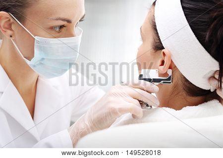 Professional ear piercing. Beautician pierces the ears of the woman in the beauty salon.