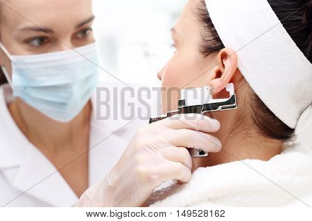 Ear piercing in cosmetic surgery. Beautician pierces the ears of the woman in the beauty salon.