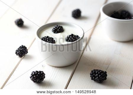 Blackberries in white yogurt on wooden table.