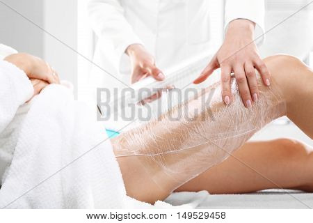 Care treatment, slimming body. Beautician woman's body wrapped with foil