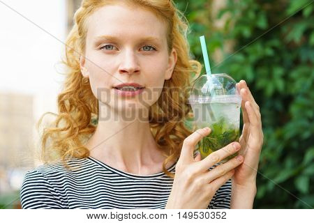 Closeup portrait of beautiful young woman with refreshing drink on hot summer day