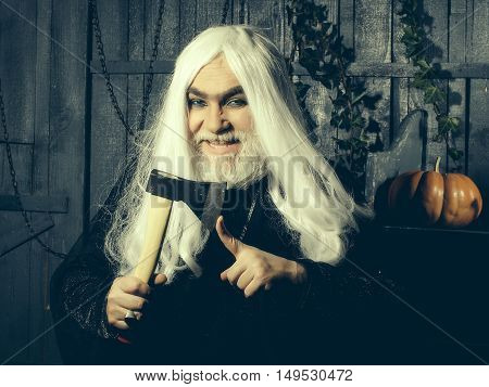 Old wizard with white long hair in black robe with demonic smile hold ax near finger in wooden house