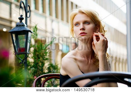 Beautiful blond woman waiting at a table in a cafe, outdoors, looking sideways