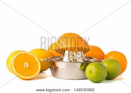 Orange Half On Steel Juicer With Whole Citrus Fruits
