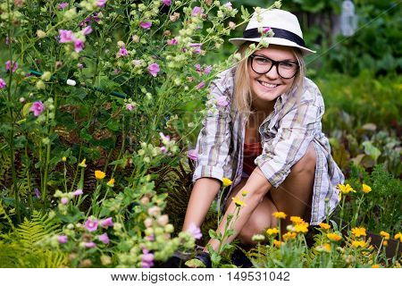 Portrait of beautiful caucasian smiling woman working in garden and care of flowers