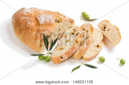 Traditional white bread with olives decorated with raw olives fruit with green leaves isolated on white background.