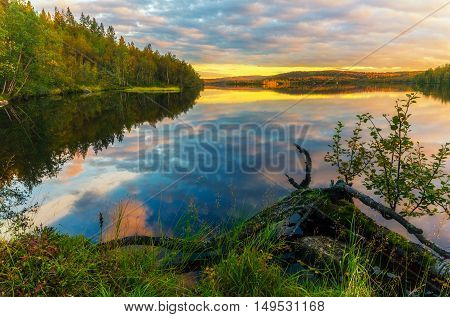 Sunset with colorful clouds over the lake in the autumn forest