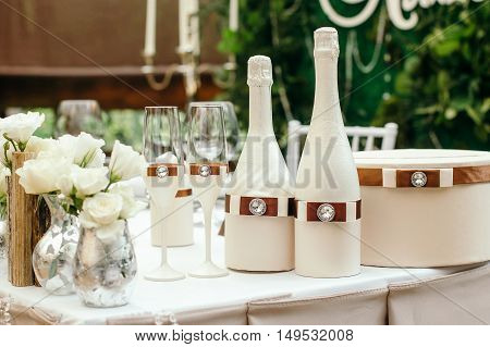 Wedding event. Chiavari chairs on the covered wooden deck. On a table decorated with a bottle of champagne and glasses. On the table box for gifts.