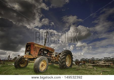 Vintage tractor in field against a dynamic cloudy blue sky background