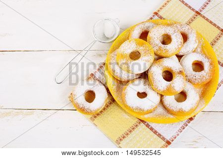 Donuts served on yellow plate top view copy space. Sweet dessert pastry doughnuts. Hanukkah sweet donuts.