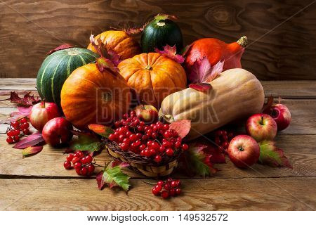 Fall concept with pumpkins apples and berries. Thanksgiving background with seasonal vegetables and fruits. Abundant harvest background.