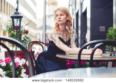 Ginger woman in long black dress is sitting in outdoor cafe, photo toned