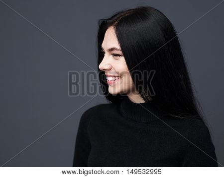 Beautiful brunette girl smiling face in profile gray background