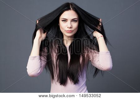 Young beautiful brunette woman is stroking the hair and playing with it gray background