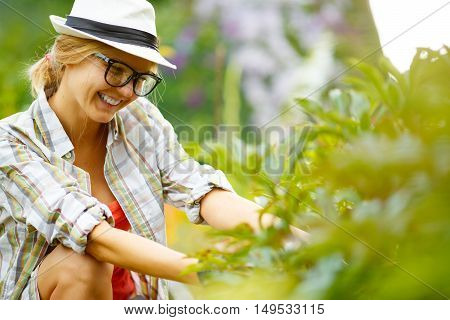 smiling young blonde woman in glasses and hat in garden