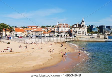 Cascais, Portugal - October 23, 2014. Praia da Ribeira beach in Cascais, with historic and commercial buildings in the distance and people.
