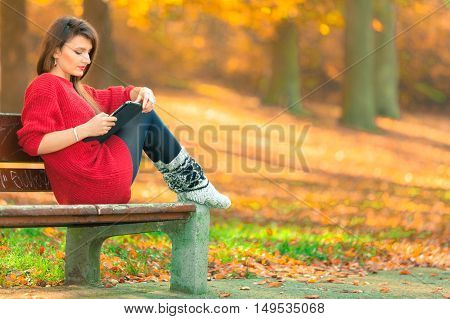 Woman On Bench In Park With Tablet.