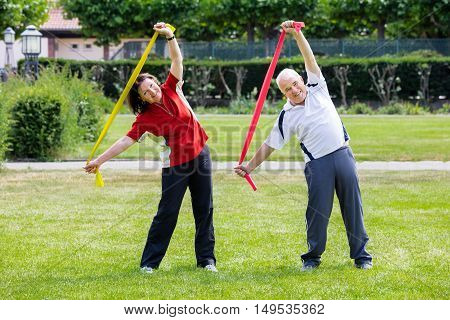 Happy Senior Couple Exercising With Yoga Belt In Park