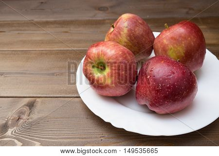 Four Fresh Red Apples In White Plate On Wooden Background