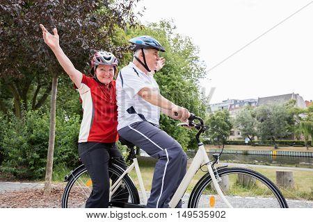 Elderly Happy Senior Couple Ride On Bicycle