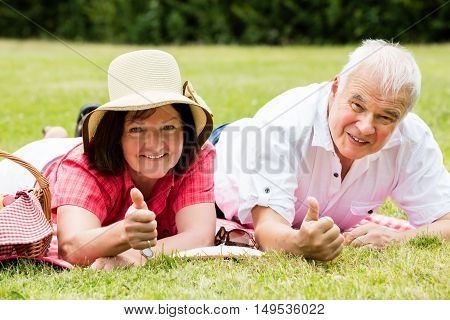 Senior Couple Lying In Park Showing Thumbs Up