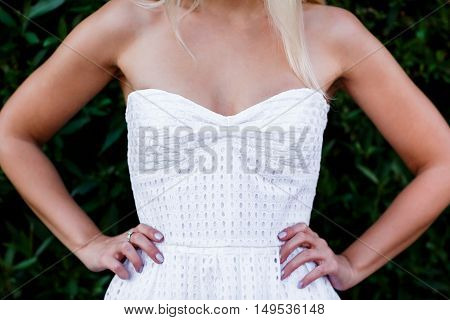 Portrait of blond woman in white dress with bare shoulders. Part body closeup. Outdoor