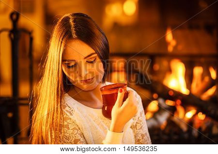 Woman drinking cup of coffee relaxing at fireplace. Young girl with hot beverage heating warming up. Winter at home.