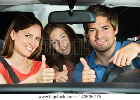 Happy Young Couple Driving In Car With Their Daughter
