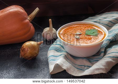 Orange pumpkin soup puree on dark table. Onion, garlic and fresh pumpkin vegetable on background. Healthy meal.