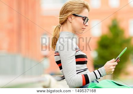 Young woman using tablet sitting on bench outdoor